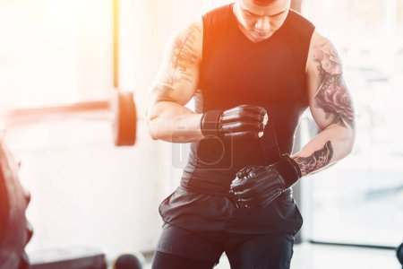 cropped view of young sportsman wearing boxing gloves at gym in sunlight