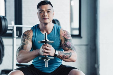 concentrated young asian sportsman exercising with dumbbell in gym and looking at camera