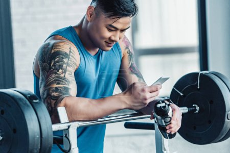 smiling tattooed young sportsman using smartphone in gym