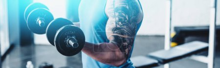 Photo for Partial view of sportsman exercising with dumbbells in gym - Royalty Free Image