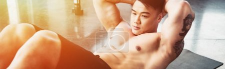 Photo for Young asian sportsman doing abs exercise on fitness mat at gym in sunlight - Royalty Free Image