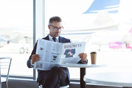 adult businessman reading newspaper in cafe at airport