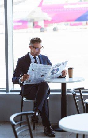 Adult homme beau lire le journal au café à l'aéroport