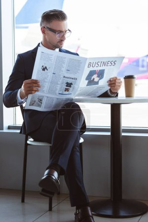 homme d'affaires adulte lisant journal dans café à l'aéroport