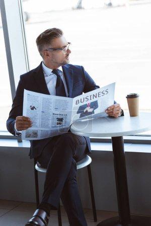 homme d'affaires adulte lire journaux et regardant la fenêtre à l'aéroport