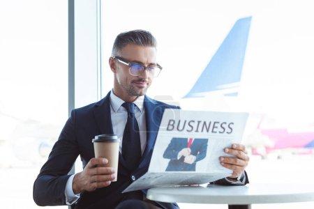 adulte beau homme d'affaires lire journaux et tenant le café pour aller à l'aéroport