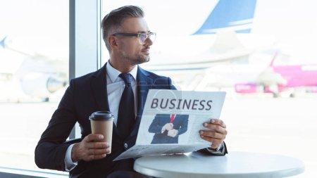 Photo pour Adulte beau homme d'affaires café d'aller lire le journal et en regardant la fenêtre à l'aéroport - image libre de droit