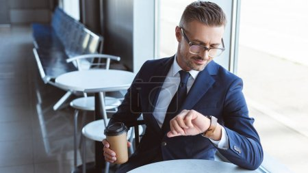 handsome businessman in glasses holding coffee to go and looking at watches on hand
