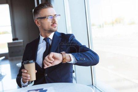 Photo pour Bel homme d'affaires dans des verres avec café pour aller et montres en regardant fenêtre en aéroport - image libre de droit