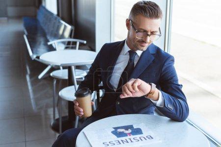 bel homme d'affaires dans des verres tenant café pour aller et regarder les montres sur place