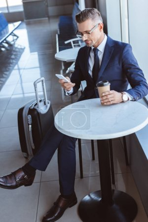 adult businessman using smartphone and drinking coffee at airport