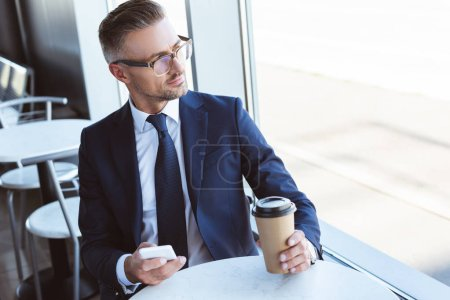 Photo for Adult handsome businessman in glasses using smartphone and looking at window at airport - Royalty Free Image