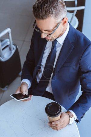 Foto de Apuesto hombre de negocios en vasos con café para llevar y equipaje con smartphone en aeropuerto - Imagen libre de derechos