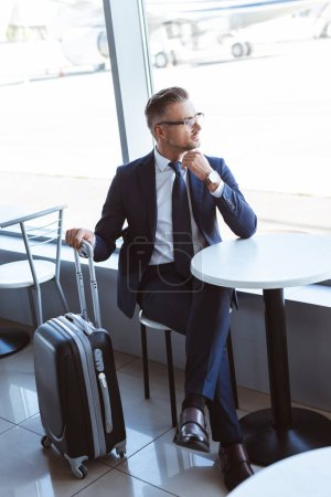 adult businessman with travel bag sitting at table in airport