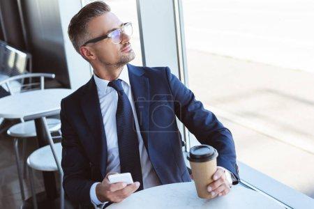 Photo pour Adulte homme d'affaires dans des verres tenant smartphone et en regardant la fenêtre à l'aéroport - image libre de droit