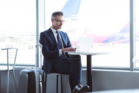 adult businessman in glasses typing on laptop at airport