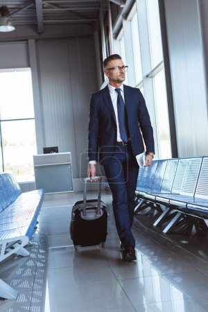 handsome businessman in glasses walking along departure lounge in airport