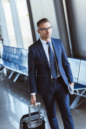 adult handsome businessman in glasses with baggage walking at airport