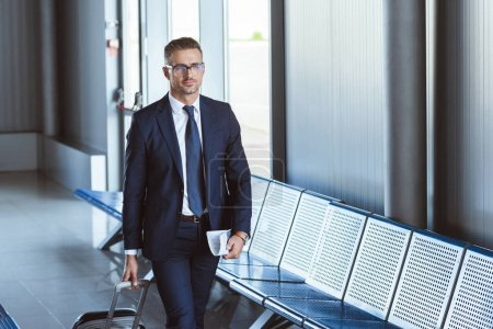 adult handsome businessman in glasses with baggage and tickets walking at airport
