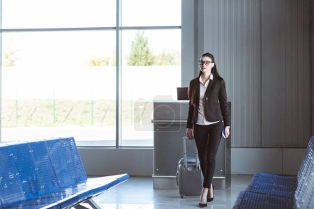 young beautiful businesswoman walking with baggage at airport