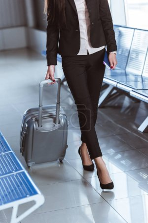 close up of y businesswoman walking with baggage in departure lounge at airport