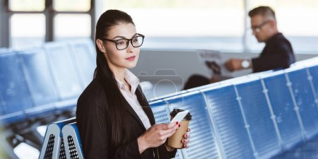 young businesswoman sitting with smartphone and coffee to go at airport