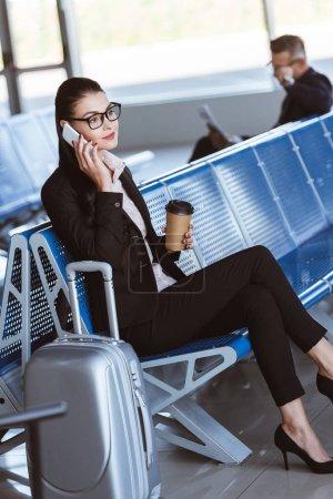 jeune femme d'affaires dans des verres avec café pour aller parler sur smartphone à l'aéroport