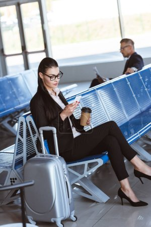 young businesswoman in glasses with baggage using smartphone at airport
