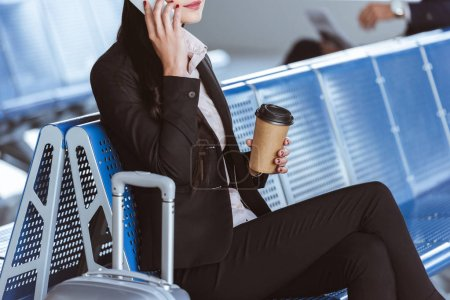 close up of young businesswoman in glasses with baggage using smartphone at airport