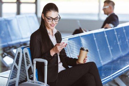 Photo pour Jeune femme souriante dans des verres avec café pour aller à l'aide de smartphone en salle d'embarquement à l'aéroport - image libre de droit