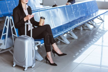 businesswoman with coffee to go using smartphone in departure lounge at airport