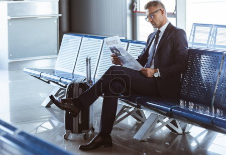 adult businessman sitting at departure lounge at airport and reading newspaper