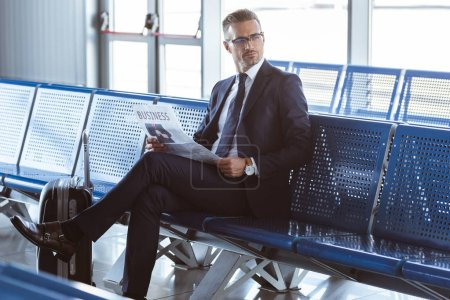 adult businessman in glasses sitting at departure lounge at airport and reading newspaper