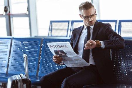 Adult homme assis avec journal à la salle d'embarquement à l'aéroport et regardant montre