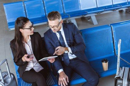Foto de Empresario adulto y empresaria sentado en el aeropuerto y el uso de tableta digital - Imagen libre de derechos