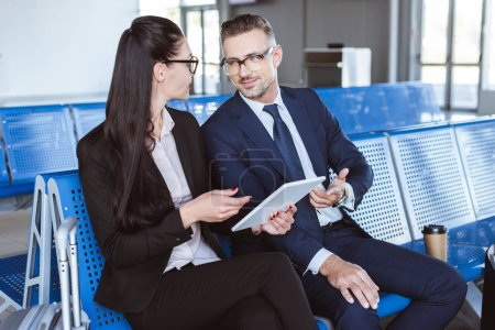 adult businessman and businesswoman sitting at departure lounge in airport and using digital tablet
