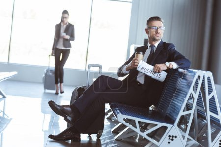 adult businessman sitting in departure lounge while businesswoman walking in airport