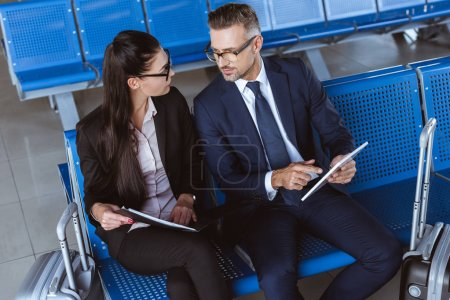 adult businessman using digital tablet while businesswoman holding black folder at departure lounge in airport