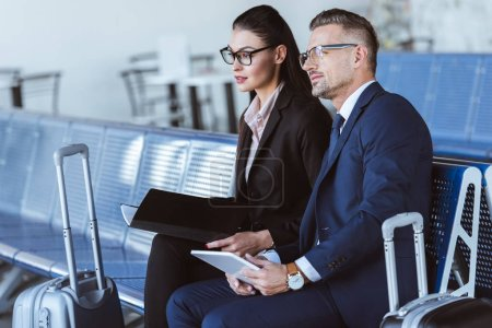 Photo for Adult businessman and businesswoman sitting at departure lounge in airport - Royalty Free Image
