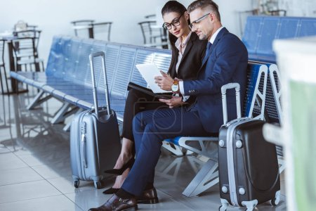 Photo for Adult businessman and businesswoman sitting at departure lounge and using digital tablet in airport - Royalty Free Image