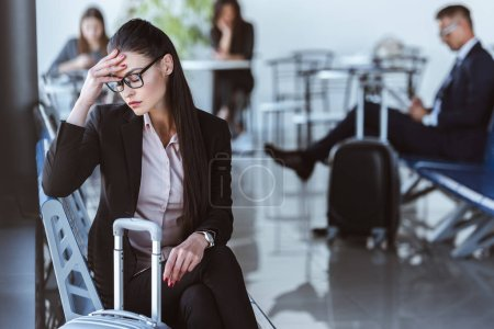 tired businesswoman sitting in departure lounge at airport