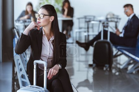adult businesswoman sitting in departure lounge at airport