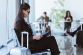 adult businesswoman with black folder sitting at departure lounge in airport