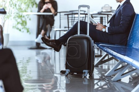 businessman with digital tablet sitting at departure lounge in airport