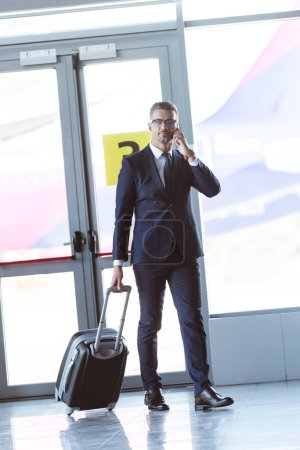adult handsome businessman in glasses with smartphone walking at airport