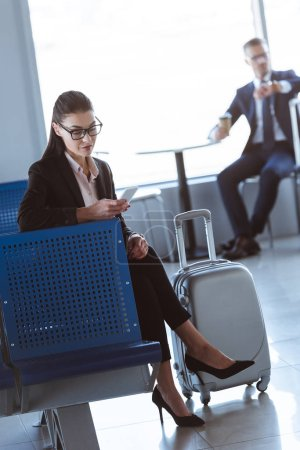 young businesswoman using smartphone while businessman sitting with coffee to go in airport