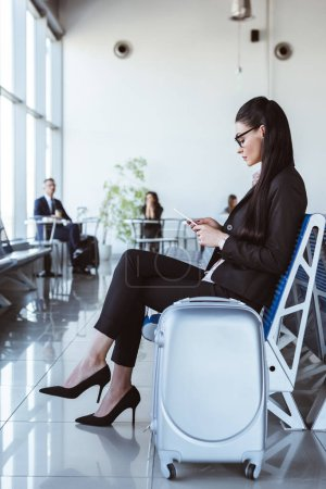 young businesswoman in glasses with smartphone sitting at departure lounge in airport
