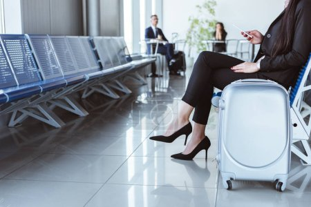 Photo for Young businesswoman with smartphone and luggage sitting at departure lounge in airport - Royalty Free Image