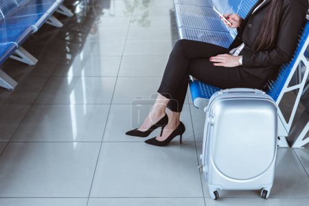 young businesswoman with smartphone and luggage sitting at departure lounge in airport