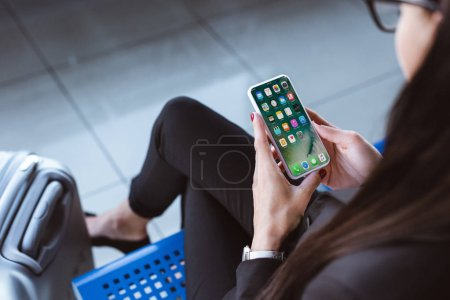 young businesswoman sitting at departure lounge in airport and using smartphone